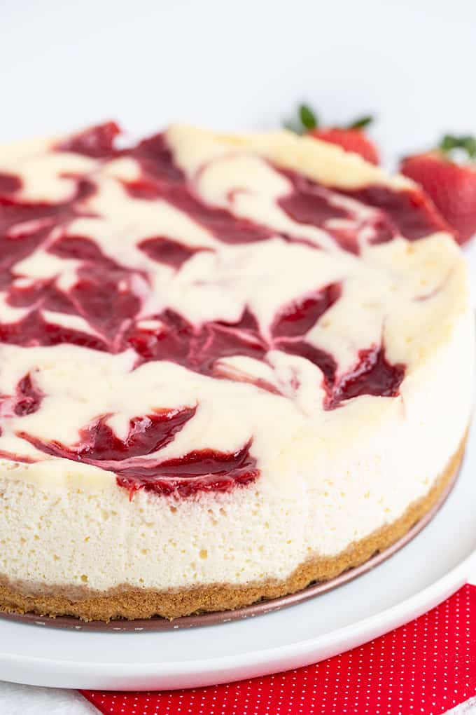 Photo showing the side and top of the cheesecake while it's sitting on a white plate with a red fabric under it