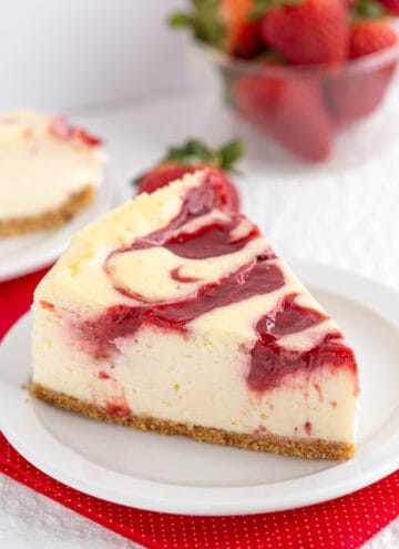 a slice of cheesecake with a strawberry swirl on top on a small white plate
