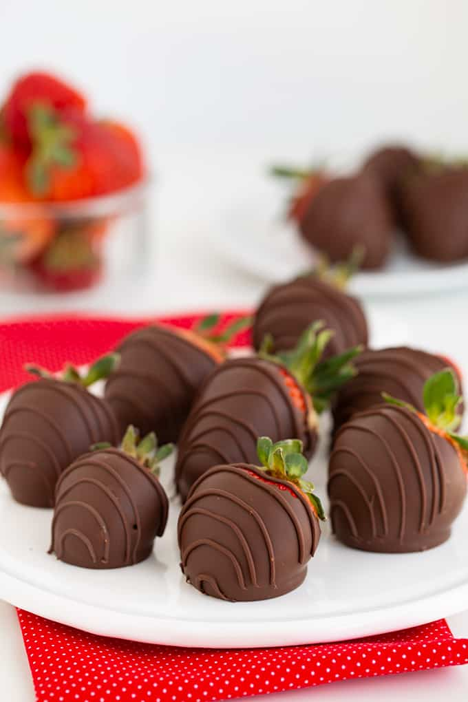 Chocolate Covered Strawberries on a white plate with a red linen under it