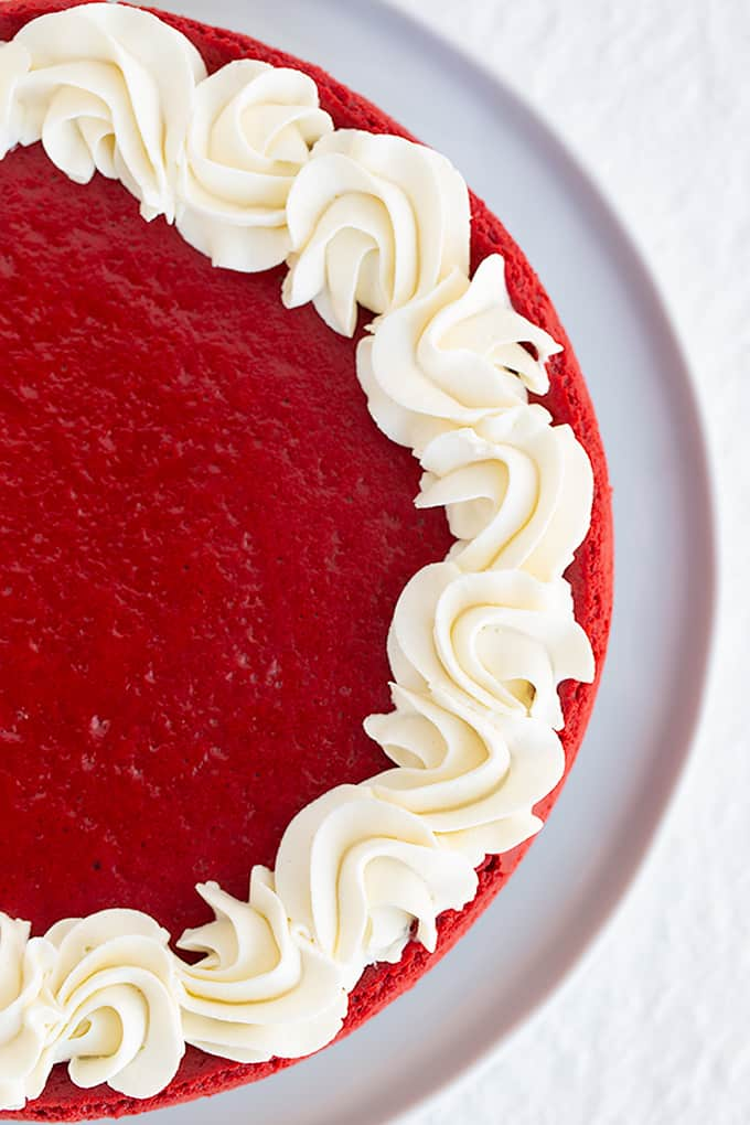 overhead photo of red velvet cheesecake on a white plate with swirls of whipped cream