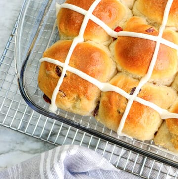 hot cross buns in a baking dish with a wire rack and linen under it