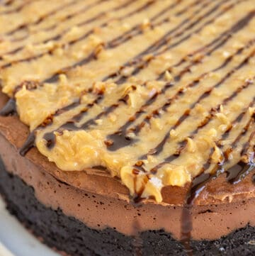 showing the topping on the german chocolate cheesecake and the side of the cheesecake sitting on a white plate