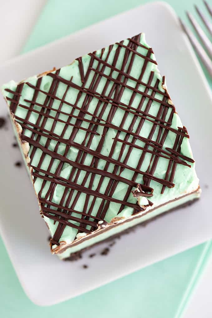 overhead photo of a slice of dessert on a white plate with a mint fabric under plate