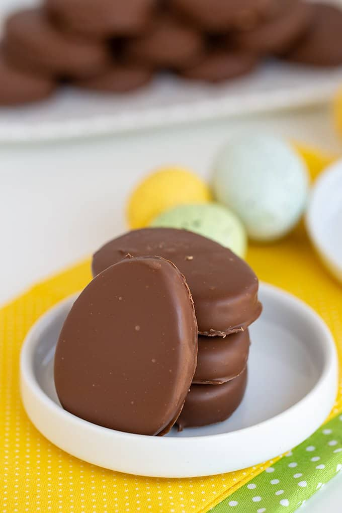 peanut butter eggs stacked with a single egg leaned against the stack on a white plate with speckled eggs behind it