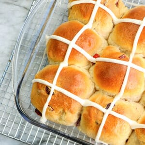 square image of a glass pan full of hot cross buns sitting on a wire rack