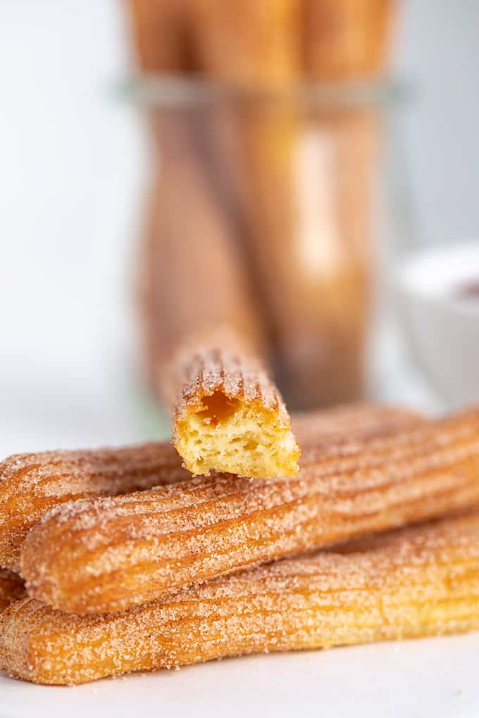 a churro broke in half to show inside sitting on top of a stack of churros