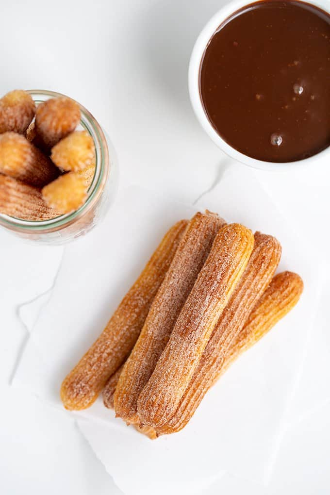 overhead photo of stacked churros on parchment paper with dipping sauce