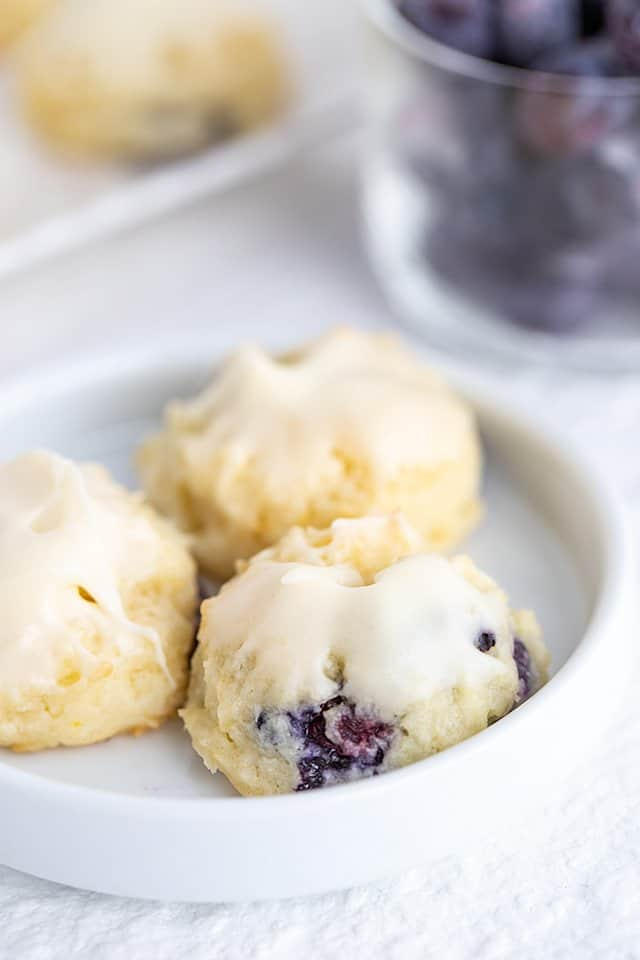 cheesecake cookies on a small white plate with a bowl of blueberries behind it