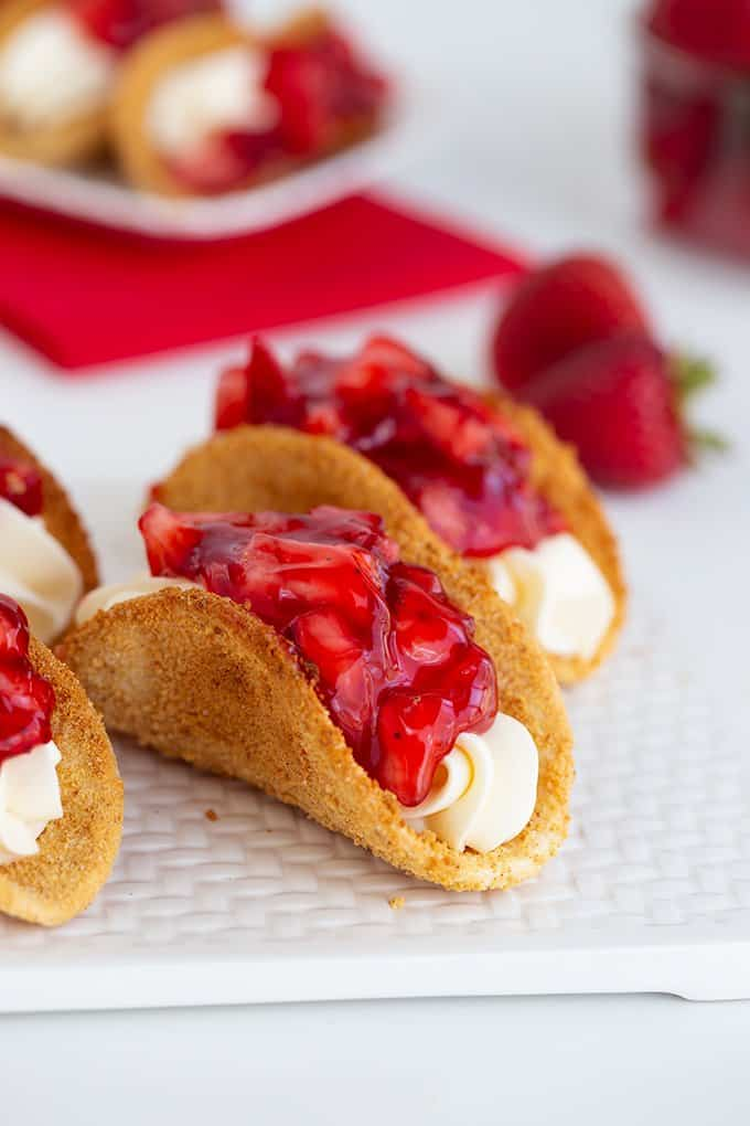 cheesecake tacos on a white cutting board on a white surface