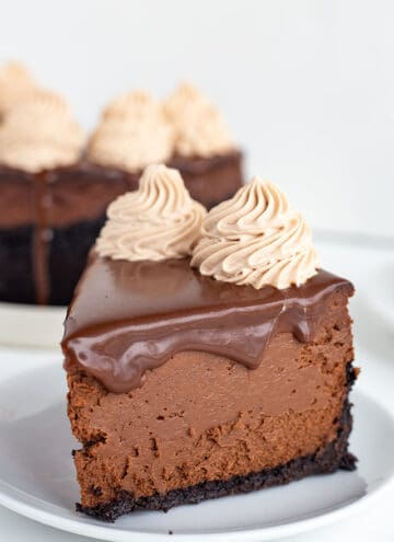 close up of a slice of chocolate cheesecake on a small white plate with the rest of the cheesecake behind it