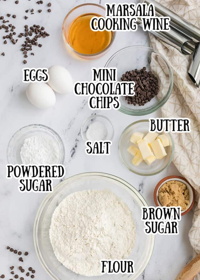 overhead photo of the cannoli shell ingredients laying out on a marble surface with what they are in text by each ingredient