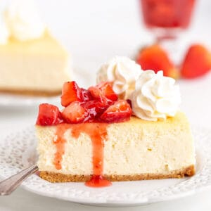 square image of a slice of cheesecake on a white plate with a fork
