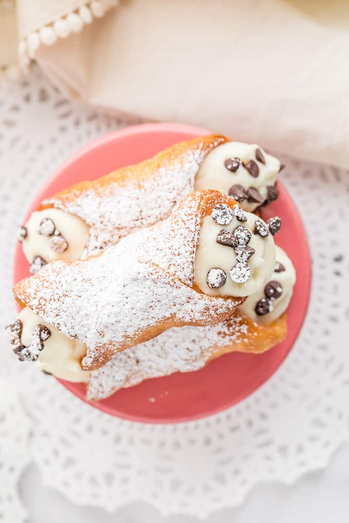 overhead photo of filled cannoli shells on a pink stand with a doilie under it