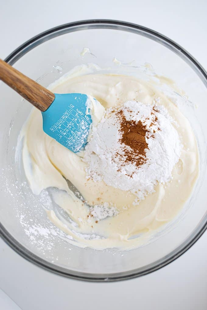 ingredients to make the cannoli filling in a glass bowl on a white surface