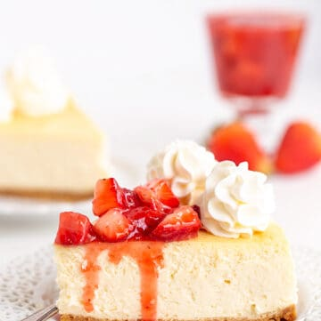 image of a slice of cheesecake on a white plate with a fork and strawberry sauce dripping down the cheesecake