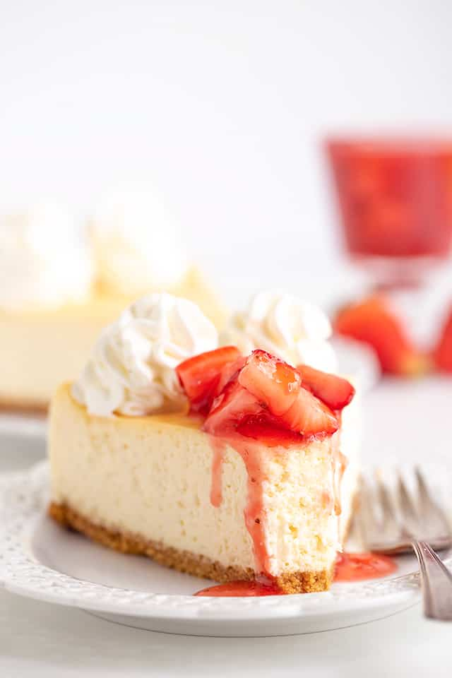 slice of cheesecake on a white plate with a bite taken out and a fork on the plate