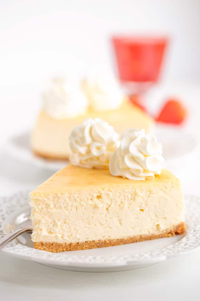 plain cheesecake on a white plate with strawberry sauce behind the plate