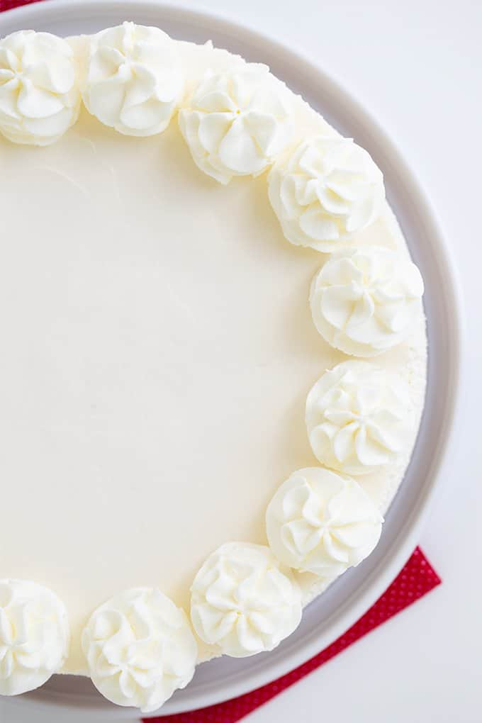 overhead image of a no bake cheesecake on a white platter on a white surface