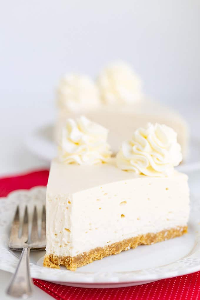 slice of cheesecake on a white plate with a bite taken out of it and a fork on the plate