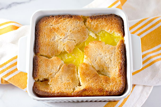 lemon cobbler in a white square baking dish with a white and yellow towel under the cobbler