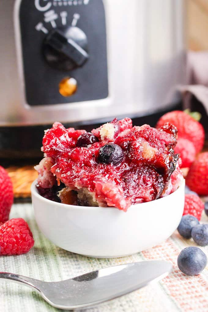 white bowl of berry cobbler with a spoon in front of it and fresh berries around it