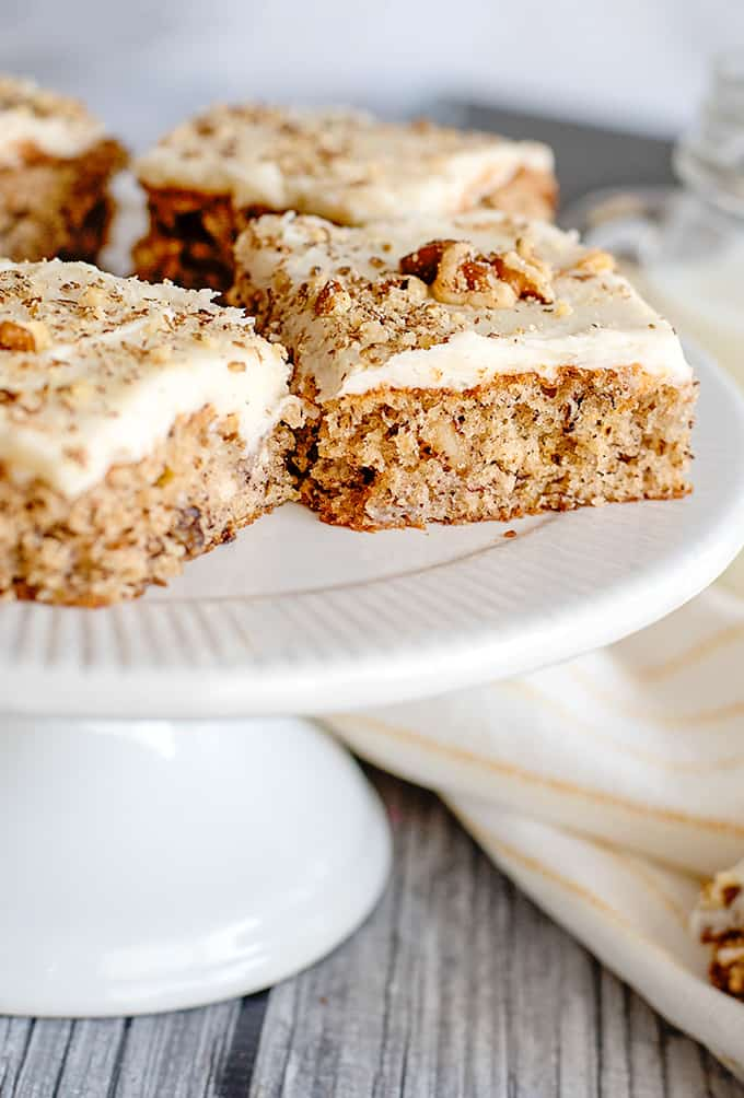 banana bars on a white cake plate with a yellow striped towel next to it