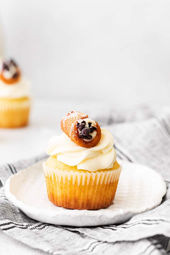 cupcakes on a white plate with a gray linen under it and a cupcake in the background