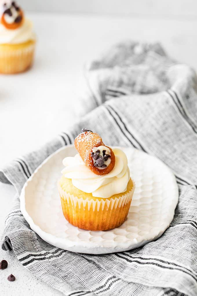 cannoli cupcakes on a small white plate with a gray linen under it
