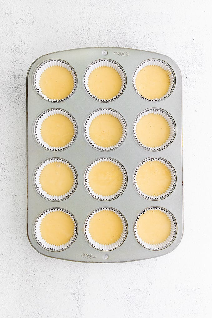 Cupcake pan with paper liners and cake batter in it on a gray surface